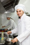 Head-cooks cooking at professional kitchen. Smiling chef with assistant cooking at professional kitchen in the restaurant. Focus on man royalty free stock photography