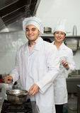 Head-cooks cooking at professional kitchen. Two smiling head-cooks cooking at professional kitchen in the cafe. Focus on man royalty free stock photography