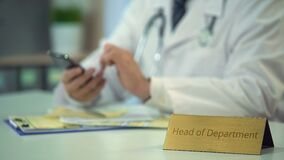 Head of department scrolling news on smartphone, doctor working in his office. Stock footage stock video