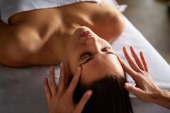 Head and face massage in spa salon royalty free stock photography