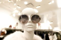 Head of female mannequin with glasses. Closeup of a female mannequin wearing an over sized round sunglasses and a fur coat stock image