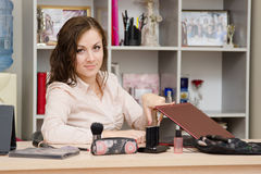 Head finished his working day. Young woman sitting at office table, laid out on the table cosmetics Royalty Free Stock Photo