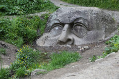 Head in the forest. Huge ancient boulder with an unknown human face on a forest path. Russia, Leningrad region Royalty Free Stock Photography