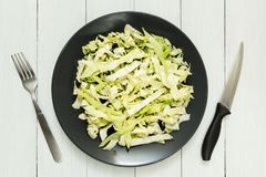 Head of fresh organic cabbage on a plate, knife and fork. White wooden table stock images