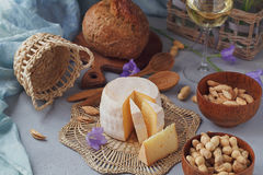 A head of fresh organic cheese served with bread, nuts, white wi Stock Photo