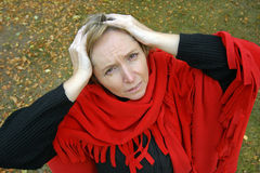 Head full of problems. A middle-aged woman keeping her hands on her head and having headache or some problems Royalty Free Stock Images
