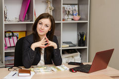 Head girl sitting at a desk with pile money her hands folded in front of him Royalty Free Stock Photography