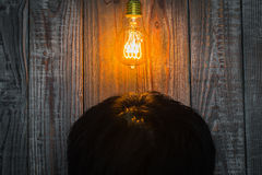 Head with Glowing bulb on the wood Stock Image