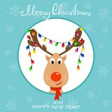 Head of reindeer with Christmas lights on blue background. The Head of Happy reindeer with red nose and Christmas lights on the antlers. Christmas character Royalty Free Stock Photo