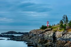 Head Harbour Lightstation. The Head Harbour Lightstation shines brightly on a gloomy morning at low tide. Also known as the East Quoddy Head. Campobello Island royalty free stock photos