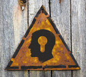 Head with a Keyhole Icon on Rusty Warning Sign. Stock Image