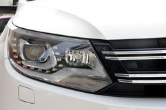 Head lamp of white car. Close-up of a new modern car head Stock Image