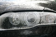 Head lights. Of a sport black car with drops of rain stock photo