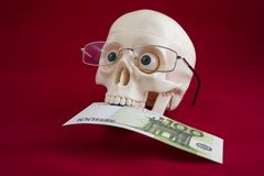 Head of a man with glasses, holds a hundred euros in his teeth royalty free stock photos