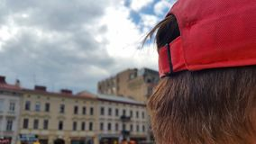 Head of a man with red hair and a red cap on the background of the houses and the sky Stock Images