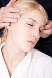 Head massage. Blond woman in white towel and mans hands massage her head royalty free stock photos