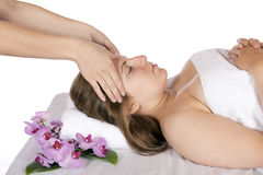 Head massage at day spa by masseuse. Spa therapy getting a head massage by technician masseuse for happy pretty young blonde woman, wrapped in towel while Royalty Free Stock Images