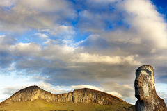 Head of moai with mountain. And a small rainbow in background royalty free stock image