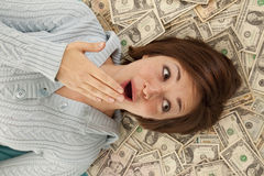 Head in money. A woman with a shocked expression on her face with her head on a pile of money Stock Photos