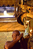 The head of monks performs a ritual, daily washing the face of Buddha stock images
