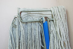 The head of a mop handle (selective focus) clasps dirty rub clot Royalty Free Stock Photography