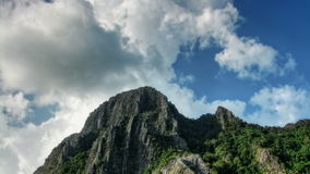 Head of a mountain and sky time lapse. The top of the cliff with trees and clouds over them time lapse stock footage