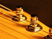 The head of the neck of an electric guitar stratocaster with pegs and strings. Artistic photo of a stringed wooden musical royalty free stock photos