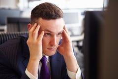 Head och skuldror av en ung stressad affärsman, huvud i händer royaltyfria foton
