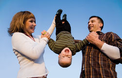 Head over heels. Happy parents play with the small son in park Royalty Free Stock Photo