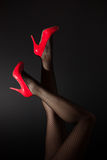 Head over high heels. A pair of sexy legs in red high heels kicked into the air on black background Stock Images