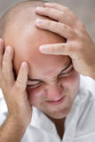 Head Pain. A young man that looks to be upset and grabbing his head in pain or anguish Stock Photography