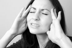 Head in pain. Young woman suffers from splitting headache Stock Photography