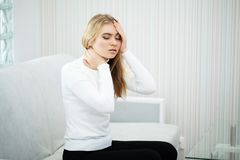 Head pain. Young woman keeping hand on her head stock photography