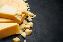 Head of parmesan or parmigiano hard cheese and pieces on concrete background. Or table Stock Images