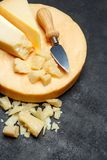 Head of parmesan or parmigiano hard cheese and pieces on concrete background. Or table Stock Image
