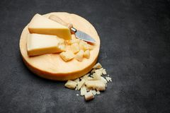 Head of parmesan or parmigiano hard cheese and pieces on concrete background. Or table Stock Photography