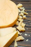 Head of parmesan or parmigiano hard cheese and pieces on wooden background. Or table Stock Images
