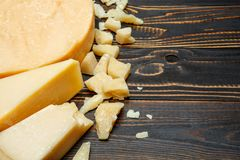 Head of parmesan or parmigiano hard cheese and pieces on wooden background. Or table Royalty Free Stock Photo