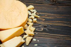 Head of parmesan or parmigiano hard cheese and pieces on wooden background. Or table Royalty Free Stock Images