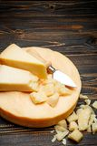 Head of parmesan or parmigiano hard cheese and pieces on wooden background. Or table Stock Photography