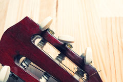 Head and pegs of a guitar on a wooden background. Stock Photo