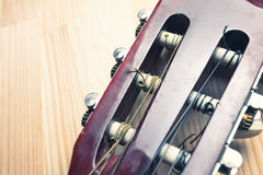 Head and pegs of a guitar on a wooden background. Royalty Free Stock Photography