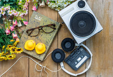Head phone cassette tape glasses diary yellow rubber duck; and p. Lastic flower; were laying down on wooden floor Stock Image