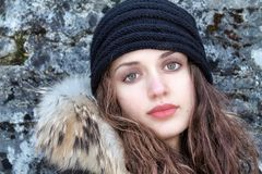 Head portrait of beautiful girl wearing winter clothes and wool blak cap royalty free stock photography