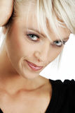 Head portrait of a beautiful woman. Head portrait of a beautiful blond woman with a lovely smooth complexion and subtle natural make-up looking at the camera Royalty Free Stock Photo