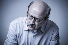 Head portrait of senior mature old man on his 60s looking sad an. D worried suffering pain and depression in sadness face expression isolated on grey background Royalty Free Stock Photos