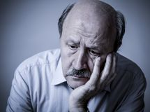 Head portrait of senior mature old man on his 60s looking sad an stock photography