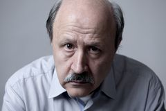 Head portrait of senior mature old man on his 60s looking sad and worried suffering pain and depression in sadness face expression. Isolated on grey background Stock Photo