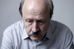 Head portrait of senior mature old man on his 60s looking sad and worried suffering pain and depression in sadness face expression. Isolated on grey background Royalty Free Stock Image