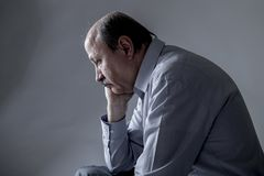 Head portrait of senior mature old man on his 60s looking sad and worried suffering pain and depression in sadness face expression. Isolated on grey background Stock Photos